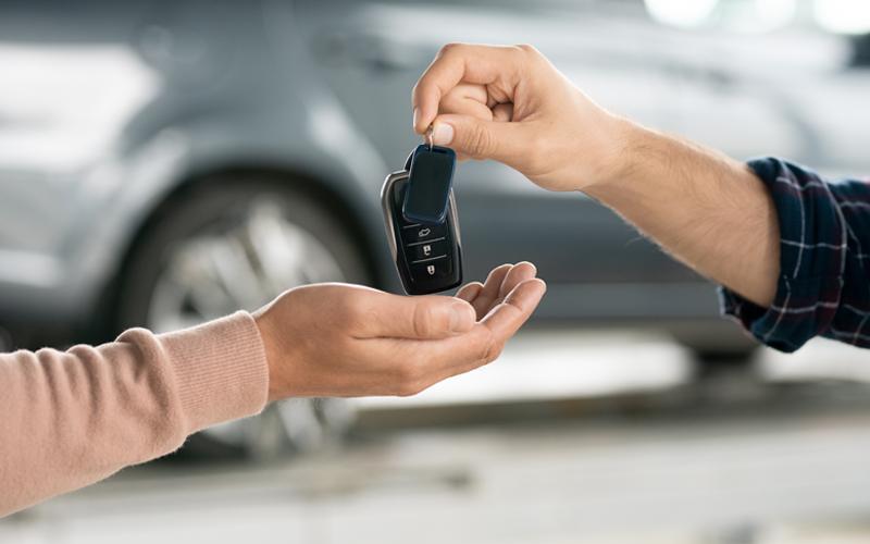 Imagem de uma mão passando uma chave de carro para outra