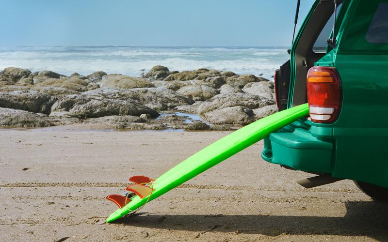 carro na praia com prancha de surf