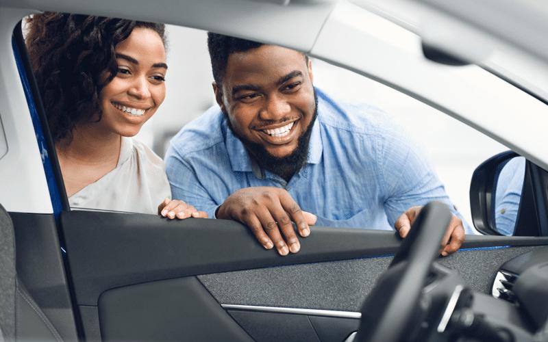 homem e mulher olhando o carro pela janela